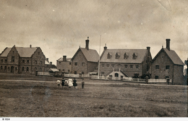 Image: six children, four girls and two boys, walk across a grass paddock in front of a complex of two storey stone buildings with steeply pitched roofs