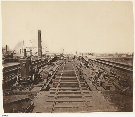 Image: A construction crew works on a bridge in a nineteenth-century port. A hard-hat diver and two well-dressed men are seated at centre right. Tall ships are visible in the adjacent river