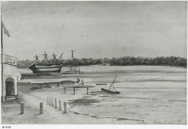 Image: A watercolour sketch of a riverbank with largely rural surroundings. The corner of a single-storey, early-nineteenth century building is visible at image left. A large three-masted sailing vessel is grounded in the middle distance