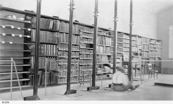 Image: shelves full of documents with person sitting on floor