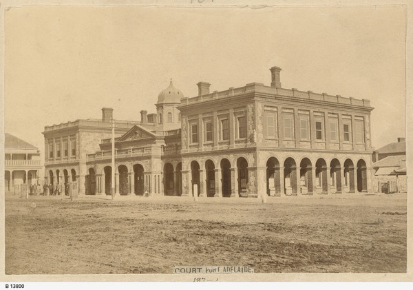 Image: A large, two-storey stone building in Victorian Italianate style. It features open archways on the ground floor, and its central section is topped by a cupola. A group of men stand in front of the left side of the building
