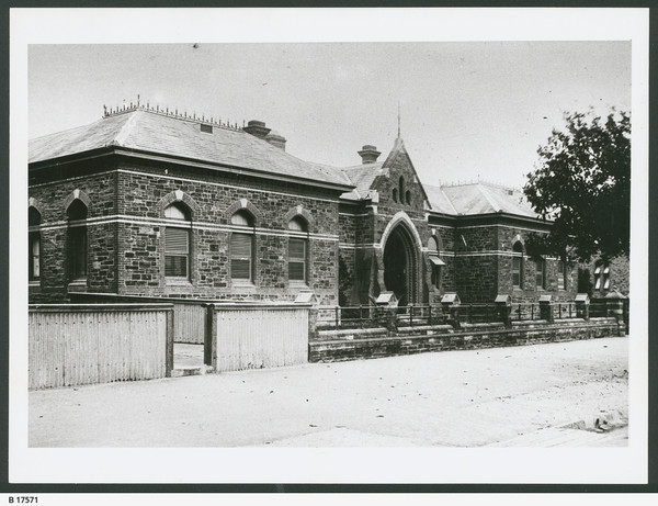 Image: a single-storey slate-roofed bluestone Gothic style building with a gabled front entrance and arched windows