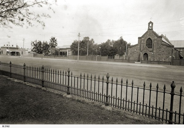 Image: A large stone church and stone house stand adjacent to one another next to a dirt street. Part of an iron fence is visible in the immediate foreground