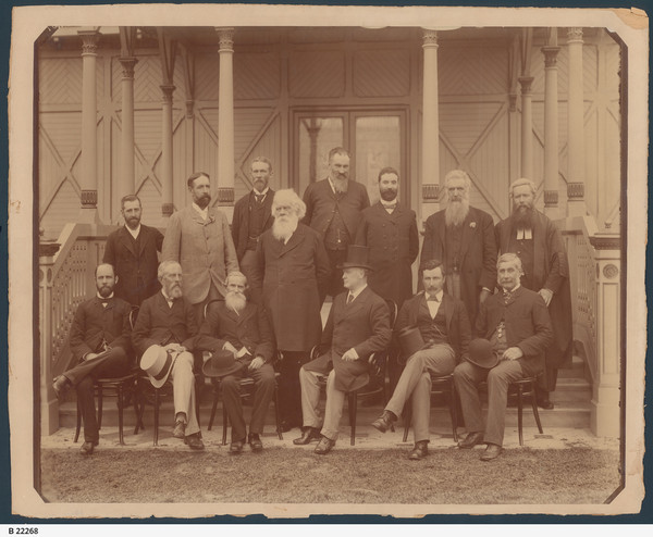 Image: caucasian men in suits pose for a photograph in front of an ornate building