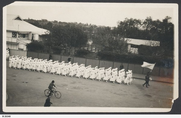 Image: group of women in white uniforms marching along the street