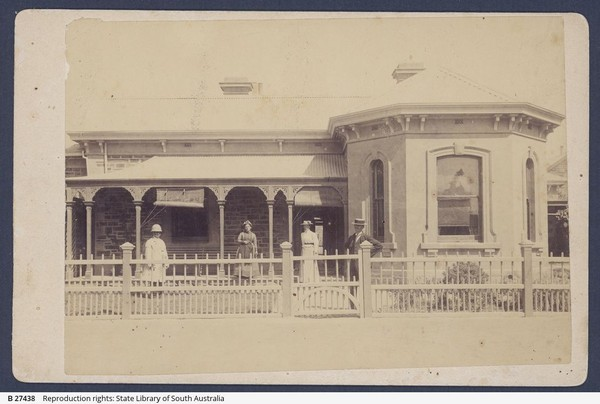 Image: A small group of men and women stand in front of a one-storey stone house with a covered verandah. A white picket fence separates the house from a dirt street