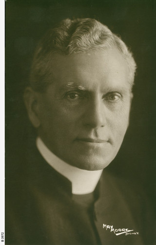 Image: Photographic head-and-shoulders portrait of a middle-aged, clean-shaven Caucasian man in an Anglican reverend's attire