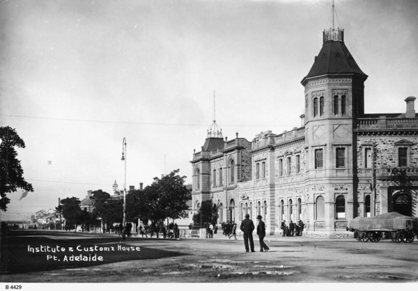 Image: A large, two-storey stone building in Victorian Italianate style. It features a large, octagonal tower with an additional storey in one corner. A horse-drawn dray is present in the street in front of the building