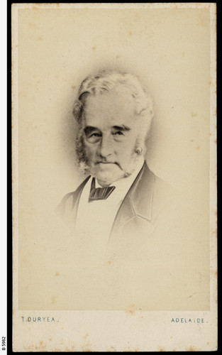 Image: Photographic head-and-shoulders portrait of an elderly Caucasian man in seven eighths view. His grey hair, sideburns and beard are neatly trimmed