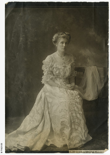 Image: Photographic portrait of a young Caucasian woman in Edwardian-era attire. She is seated and wearing a floor-length light-coloured dress with embroidered decoration
