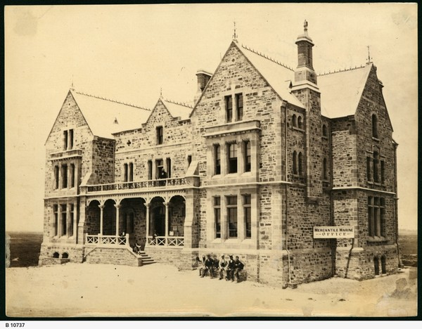Image: A large, three-storey mid-nineteenth century bluestone building sitting atop reclaimed land. A sign reading 'Mercantile Marine Office' is visible at the bottom right of the building. A group of men sit on a bench near the building entrance