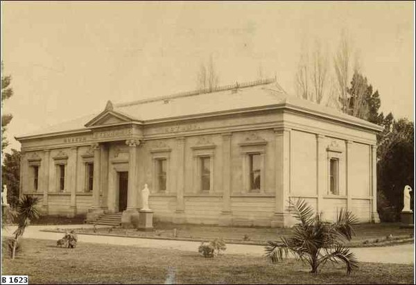 Image: Old photograph of a single storey building with a door and six window along the front and a single window visible on the adjacent side of the building.  The building also features a small portico and is reasonably ornate.