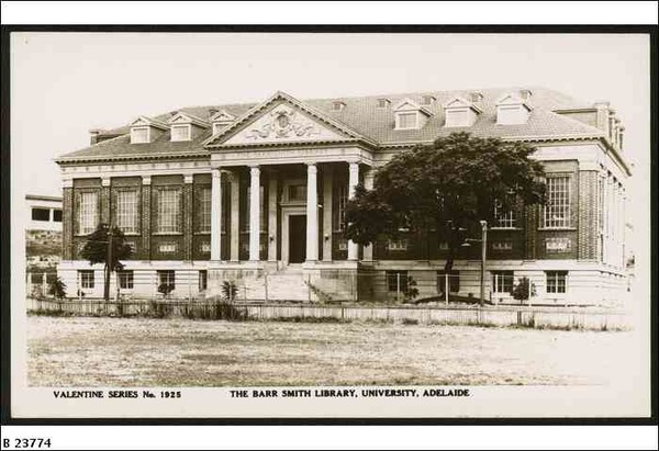 Image: A large rectangular brick building with Greek Revival-style columns flanking its main entrance