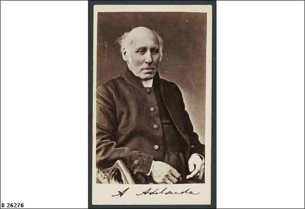 Image: Photograph of bald seated man wearing a dark coloured coat and clerical collar