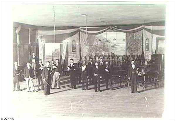 Image: a scattering of men in a large room dressed with lines of chairs and featuring a small stage with a piano.