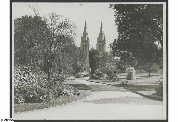 Image: Black and white photograph of a path winding through gardens towards a cathedral