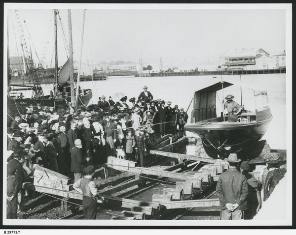 Image: A small motor vessel is launched from its construction slip into a river. A crowd of people in late-Victorian attire look on