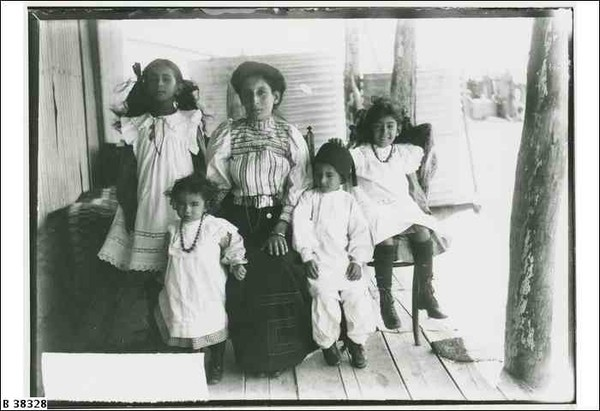 Image: A woman in Edwardian dress sits on a verandah with her four children. A corrugated water tank is visible in the background