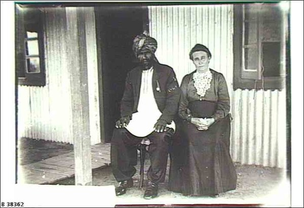 Image: Afghan man and his wife pose for photograph in front of corrugated iron home