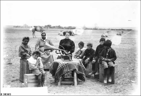 Image: A group of Afghan children and an Aboriginal woman sit around a small table, atop which sits a gramophone. A Caucasian woman in Victorian dress operates the gramophone