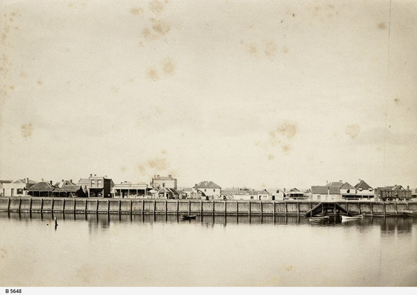 Image: A line of buildings sit atop a long wharf. In front of the wharf is a river, in which three small boats are moored