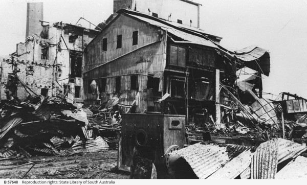 Image: A burned-out corrugated metal building stands next to the partially-destroyed wall of a multi-storey brick building. Sheets of twisted corrugated metal and other debris are visible in the foreground
