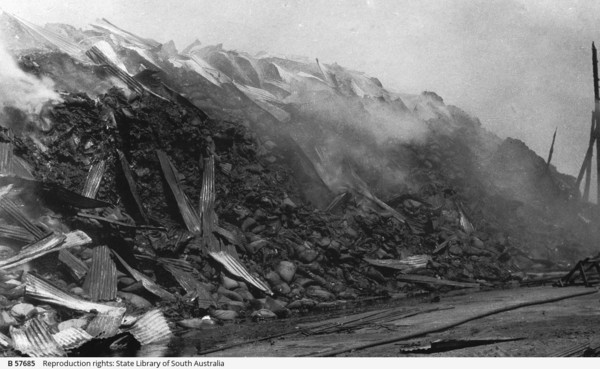 Image: A large, smouldering pile of charred gunny sacks, atop which are fragments of burned corrugated metal sheeting