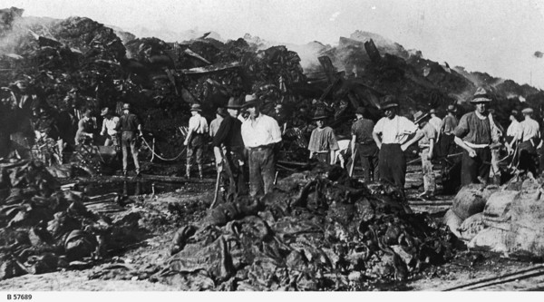 Image: A group of men dressed in work clothes and wide-brimmed hats pose for a photograph next to piles of fire-damaged sacks