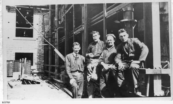 Image: A group of four men pose for a photograph outside a multi-storey brick building under construction