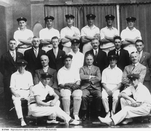 Image: A group of men in cricket uniforms poses for a photograph with other men dressed in suits