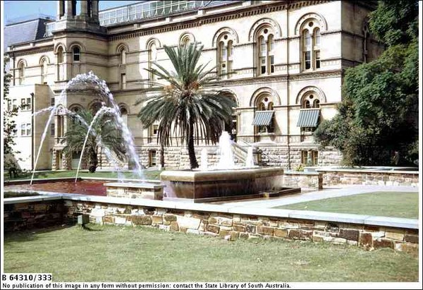 Image: stone fountain shaped like bathtub in front of stone buildings