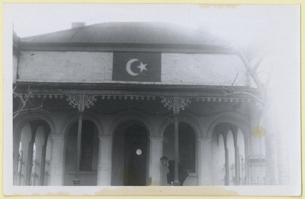 Image: A man stands outside a building with columns and a flag with star and crescent painted on one wall