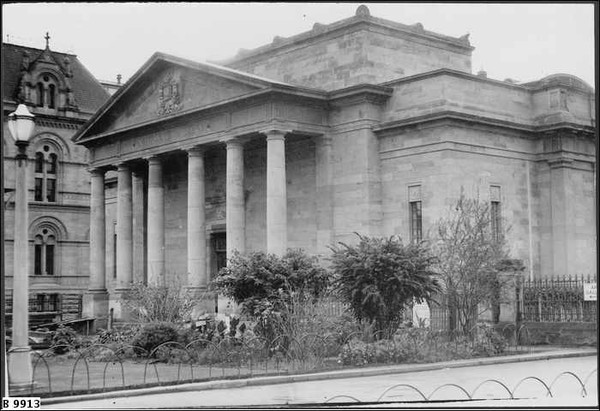Image: Image: a stone building with six columned portico and decorative pediment