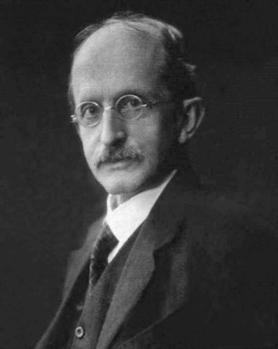 Image: A photographic portrait of a middle-aged man with a moustache and wire-rimmed spectacles