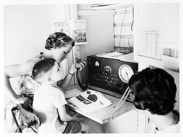Image: Two adult women and a young boy sit in front of a large two-way radio receiver. One woman holds the radio's transmitter in her hand. The boy has an open textbook in front of him