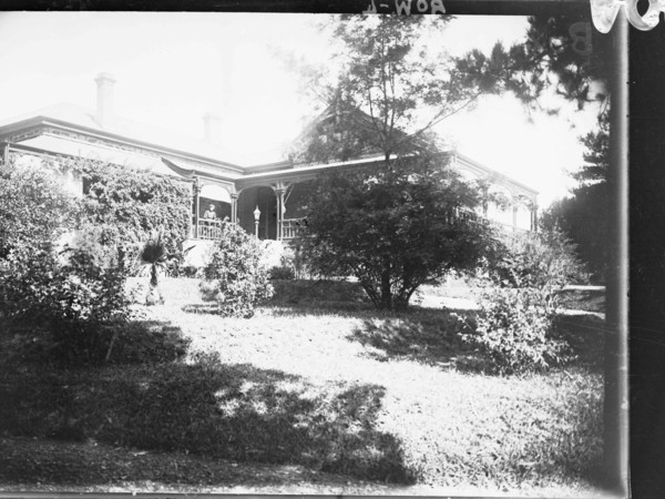 Image: A large stone house bordered on one side by a well-tended garden. A woman stands on the verandah of the house