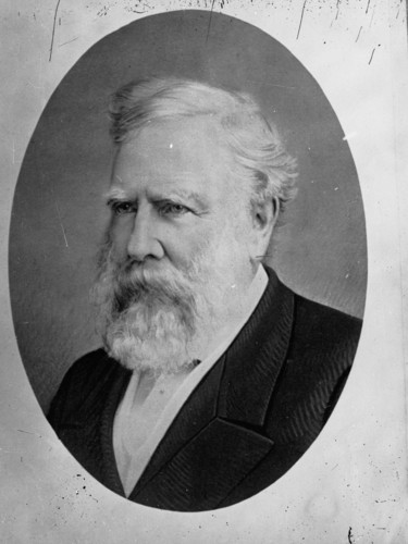 Image: A head-and-shoulders profile of a middle-aged man with white hair and beard. The man is wearing late-Victorian attire