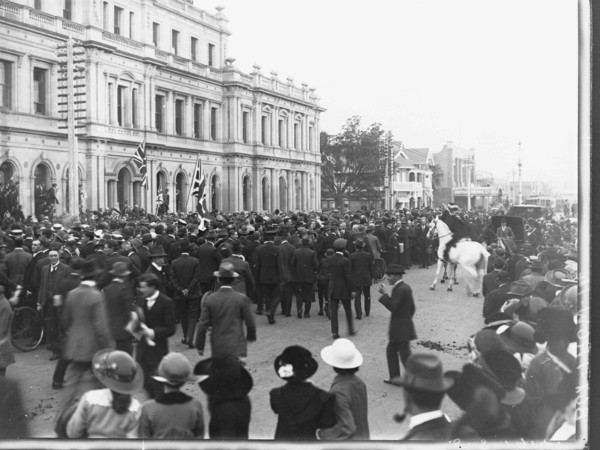 Image: crowd of people in front of large three story building