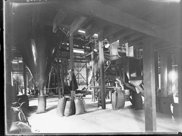 Image: The interior of a large warehouse with belt-driven machinery. Full gunny sacks are arranged near the machinery, and one sack is positioned beneath a large funnel