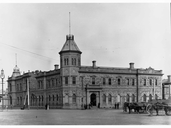 Image: A large, two-storey stone building in Victorian Italianate style. It features a large, octagonal tower with an additional storey in one corner. Two horse-drawn carts are present in the street in front of the building