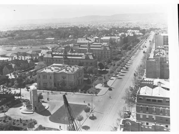 Image: Image: Black and white photograph of a tree lined boulevard, as viewed from the roof of a building. The buildings lining one side of the road are grand stone constructions and are surrounded by formal gardens.