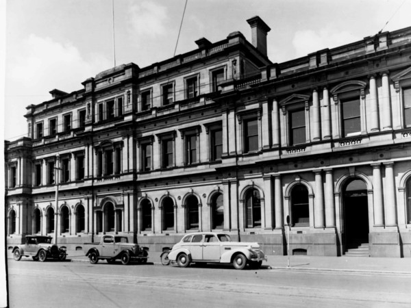 Image: three cars parked in front of long, three story building