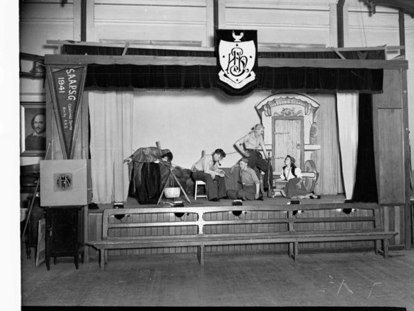 Image: Five teenagers, three boys and two girls, act out a scene on a small stage. The boys wear workers costumes, one girl is draped in a shawl and the other wears a full layered skirt, white blouse and vest. The props include a cook pot and gypsy wagon.