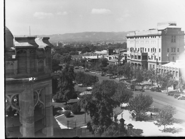Image: A large six storey concrete building, with two storey columns flanking its entrance way, dominates one side of a tree lined street upon which a tram travels and 1930s era cars are parked.