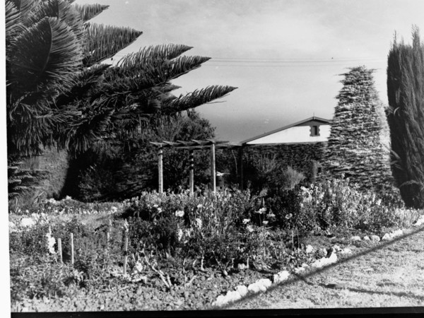 Image: A formal plant and flower garden is located in front of a small, single-storey cottage