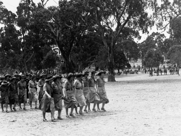 Image: Two lines of girl guides marching in a national park with tall trees in the background