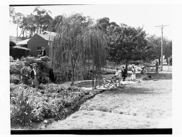 Image: Five women and two men pose for a photograph in a small terraced garden. A small pool in the middle of the garden is flanked by two trees and a stone wall