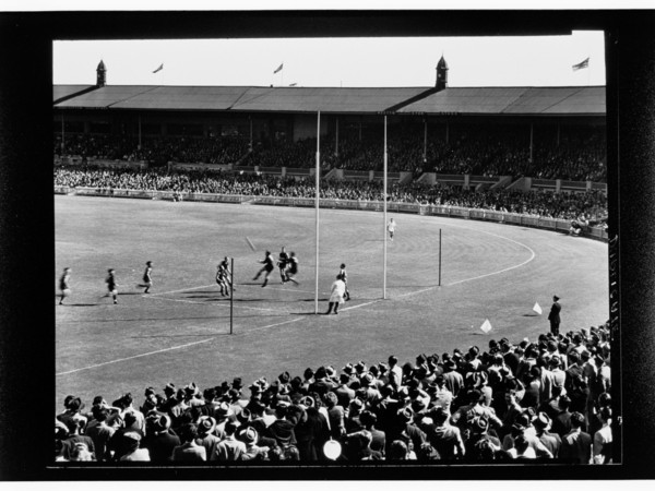 Image: A group of men play Australian Rules Football on an unidentified oval