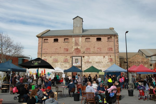 Image: A large group of people sit at tables and examine market stalls in front of a large, multi-storey historic stone building