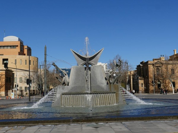 Image: grey three pointed fountain with city buildings in background